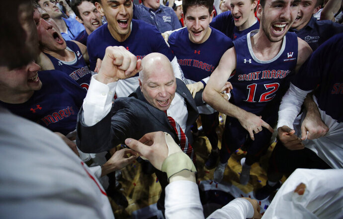FILE - In this March 12, 2019, file photo, St. Mary's head coach Randy Bennett celebrates with his team after they defeated Gonzaga 60-47 in an NCAA college basketball game in the championship of the West Coast Conference tournament in Las Vegas. In all of his successful years at tiny Saint Mary's College and the challenge of turning around a program almost two decades ago, this NCAA Tournament berth is perhaps the most gratifying yet for Bennett. (AP Photo/John Locher, File)