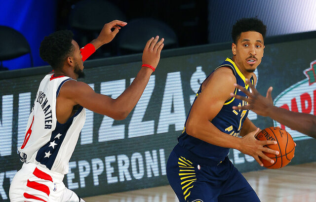 Indiana Pacers Malcolm Brogdon (7) handles the ball as Washington Wizards Troy Brown Jr. (6) defends during the first half of an NBA basketball game Monday, Aug. 3, 2020, in Lake Buena Vista, Fla. (Mike Ehrmann/Pool Photo via AP)