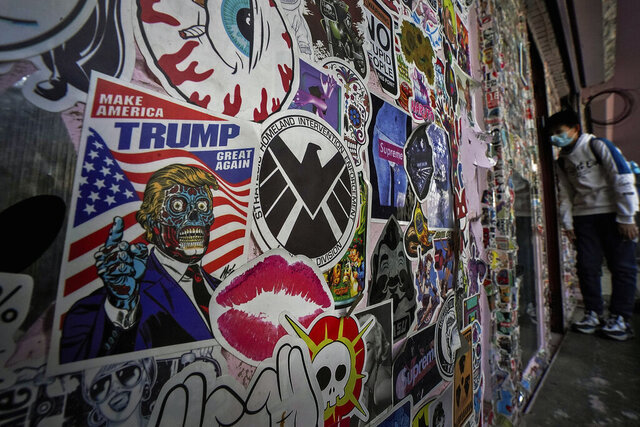 A man wearing a face mask to help curb the spread of the coronavirus looks into a souvenir shop displaying various of stickers, one of them showing a former U.S. President Donald Trump caricature, in Beijing, Thursday, Jan. 21, 2021. China imposed sanctions on nearly 30 former Trump administration officials moments after they left office on Wednesday. In a statement released just minutes after President Joe Biden was inaugurated, Beijing slapped travel bans and business restrictions on Trump's secretary of state, Mike Pompeo, national security adviser Robert O'Brien and U.N. ambassador, Kelly Craft. (AP Photo/Andy Wong)