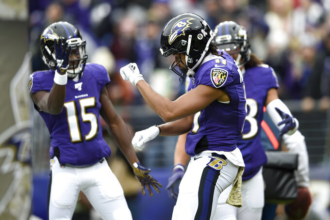 Baltimore Ravens wide receiver Seth Roberts (11) celebrates with teammates Marquise Brown (15) and Willie Snead (83) after scoring on a touchdown pass from Lamar Jackson, not visible, during the first half of an NFL football game against the Houston Texans, Sunday, Nov. 17, 2019, in Baltimore. (AP Photo/Gail Burton)