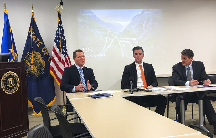 In this Friday, Nov. 8, 2019, photo, FBI Assistant Special Agent in Charge George Chamberlin, from left, speaks as Gabriel Gundersen, an FBI supervisory special agent with the Oregon Cyber Task Force, center, and Loren Cannon, FBI special agent in charge of the Portland Division, in Portland, Ore., to reporters about the rise of cybercrime in Oregon. FBI agents are warning the public about cybercrime, with the numbers of victims and money stolen soaring in sophisticated scams. In 2015, $220 million was lost to wire fraud in the United States. In 2019, losses will surpass $1.5 billion, according to WFG National Title Insurance Company. (AP Photo/Andrew Selsky)