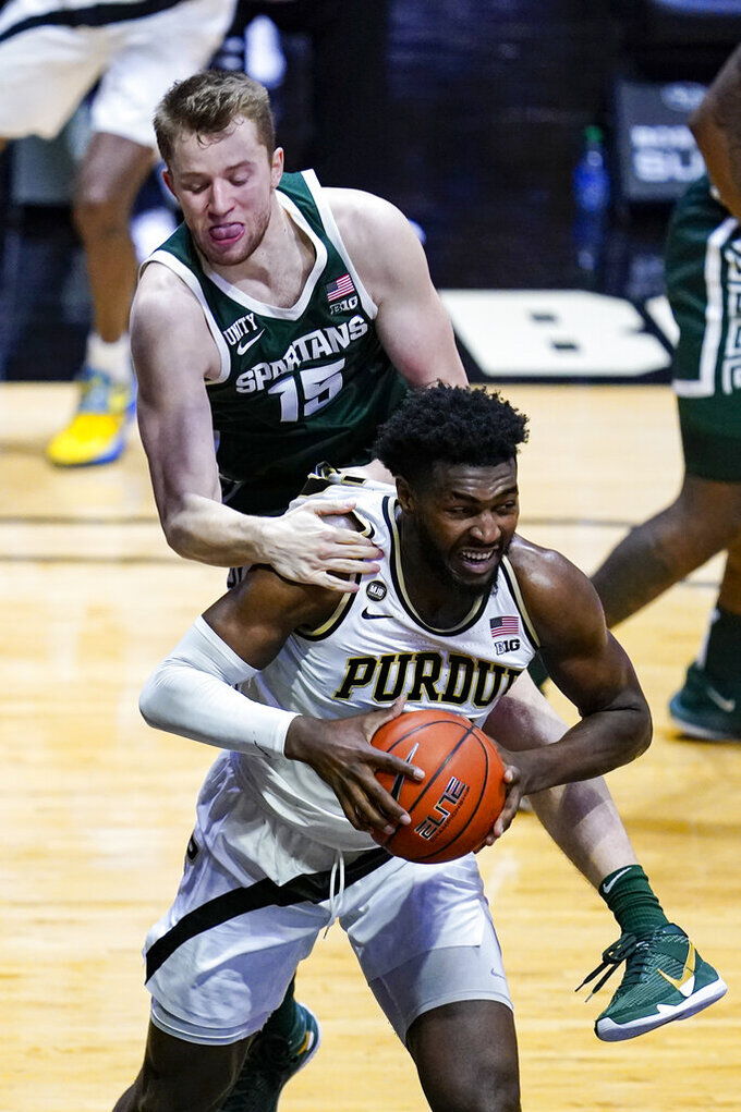 Michigan State forward Thomas Kithier (15) fouls Purdue forward Trevion Williams during the second half of an NCAA college basketball game in West Lafayette, Ind., Tuesday, Feb. 16, 2021. Purdue won 75-65. (AP Photo/Michael Conroy)