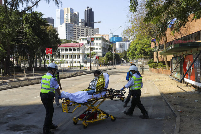 A protester is wheeled on a stretcher by first aid personnel as they leave the Polytechnic University campus in Hong Kong, Thursday, Nov. 21, 2019. A small group of protesters refused to leave Hong Kong Polytechnic University, the remnants of hundreds who took over the campus for several days. (AP Photo/Vincent Thian)