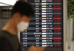 An electronic signboard shows the cancellations of domestic flights due to approaching typhoon at the arrival hall of the Gimpo Airport in Seoul, South Korea, Monday, Sept. 7, 2020. The second powerful typhoon to slam Japan in a week damaged buildings, caused blackouts in nearly half a million homes and injured 20 people on southern Japanese islands before heading to South Korea on Monday.(AP Photo/Lee Jin-man)