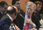 U.S. National security adviser John Bolton, right, speaks with U.S. Commerce Secretary Wilbur Ross during a conference of more than 50 nations that largely support Venezuelan opposition leader Juan Guaido in Lima, Peru, Tuesday, Aug. 6, 2019. Bolton says the U.S. will target anybody at home or abroad who supports the government of Venezuelan President Nicolas Maduro with stiff financial sanctions. Bolton spoke a day after the Trump administration announced a new round of sweeping measures aimed at pressuring Maduro from office. (AP Photo/Martin Mejia)