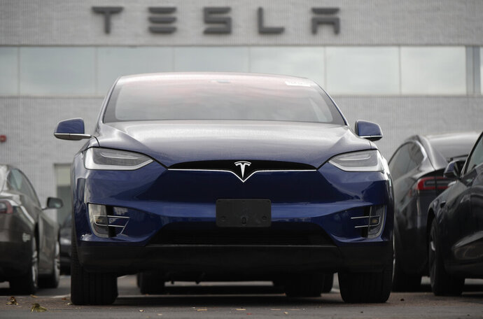 In this Oct. 20, 2019, photo an unsold 2019 Model X sits under a sign at a Tesla dealership in Littleton, Colo.  Tesla says its global deliveries rose more than 50% last year meaning the company surpassed the low end of its sales goals for 2019. The electric car maker said Friday, Jan. 3, 2020, that it delivered a record of about 112,000 vehicles in the fourth quarter and about 367,500 for the full year. Tesla previously announced that it expected to deliver 360,000 to 400,000 units worldwide last year.   (AP Photo/David Zalubowski, File)