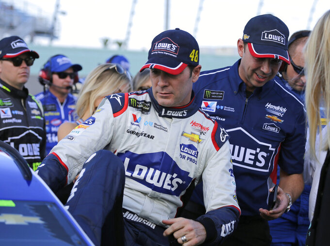 Jimmie Johnson, left, gets into his car before the NASCAR Cup Series championship auto race at Homestead-Miami Speedway, Sunday, Nov. 18, 2018, in Homestead, Fla. At right is crew chief Chad Knaus. (AP Photo/Terry Renna)