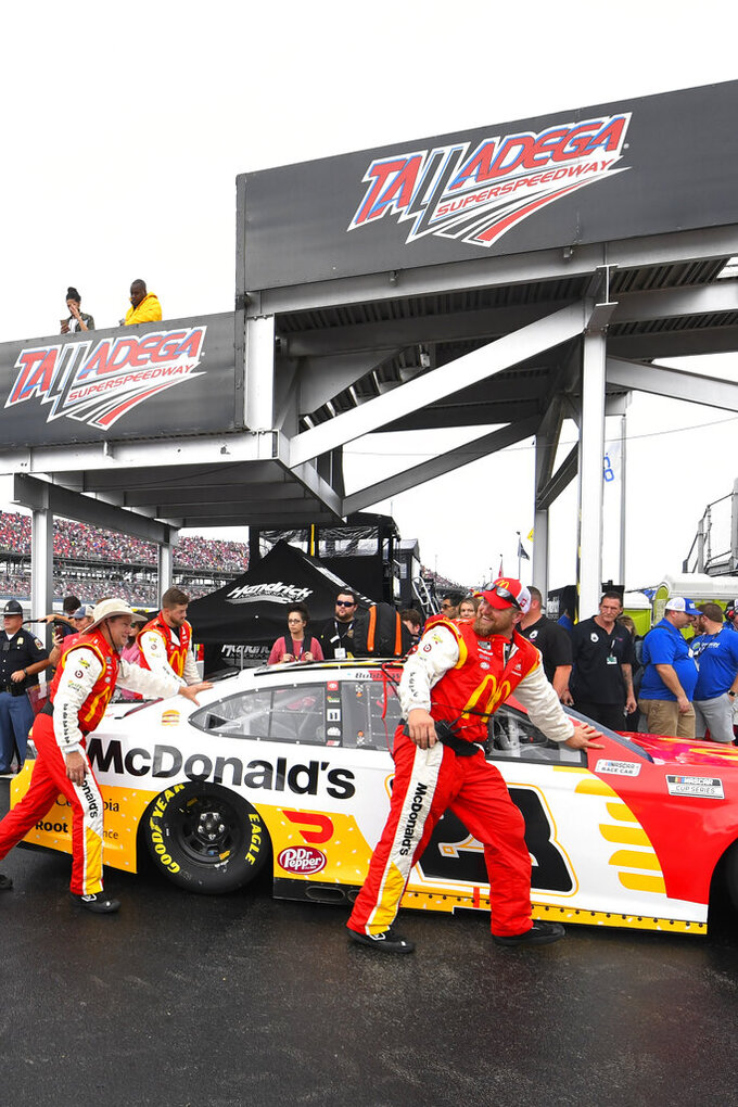 Team members of a car Bubba Wallace drives is pushed off pit row after a NASCAR Cup series auto race was postponed until tomorrow due to wet conditions, Sunday, Oct. 3, 2021, in Talladega, Ala. (AP Photo/John Amis)