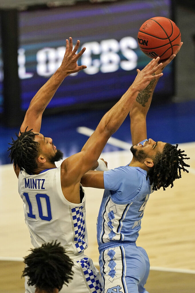 North Carolina's R.J. Davis (4) drives to the basket against Kentucky's Davion Mintz (10) in the first half of an NCAA college basketball game, Saturday, Dec. 19, 2020, in Cleveland. (AP Photo/Tony Dejak)