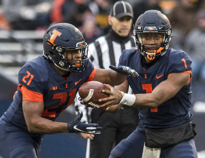 Illinois quarterback A.J. Bush, Jr. (1) hands off to running back Ra'Von Bonner (21) in the first half of a NCAA college football game against Iowa, Saturday, Nov. 17, 2018, in Champaign, Ill. (AP Photo/Holly Hart)