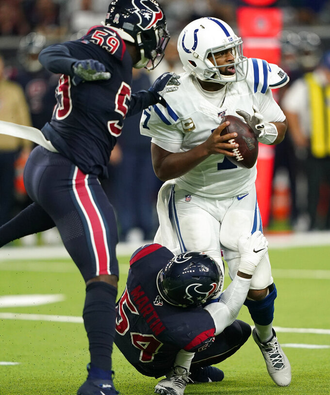 Indianapolis Colts quarterback Jacoby Brissett (7) is pressured by Houston Texans outside linebacker Whitney Mercilus (59) and linebacker Jake Martin (54) during the first half of an NFL football game Thursday, Nov. 21, 2019, in Houston. (AP Photo/David J. Phillip)