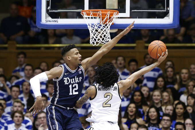 Duke forward Javin DeLaurier (12) blocks Wake Forest guard Sharone Wright Jr. (2) during the second half of an NCAA college basketball game in Durham, N.C., Saturday, Jan. 11, 2020. (AP Photo/Gerry Broome)