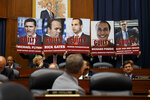 Staff members hold up posters in a House Committees on the Judiciary and Oversight and Government Reform hearing on