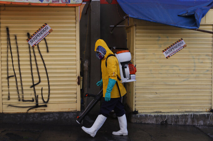 A city worker in full protective gear amid the new coronavirus pandemic disinfects the sidewalk outside the Haiti market in La Paz, Bolivia, Tuesday, June 23, 2020. Health authorities say that a butcher at the marker died several weeks ago of COVID related symptoms, prompting its closure. (AP Photo/Juan Karita)