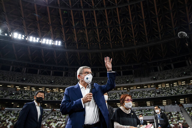 "IOC President Thomas Bach wearing a face mask waves as he speaks to the media at the National Stadium, the main venue for the 2020 Olympic and Paralympic Games postponed until July 2021 due to the coronavirus pandemic, in Tokyo Tuesday, Nov. 17, 2020. Bach said during this week's trip to Tokyo that he is ""encouraging"" all Olympic ""participants"" and fans to be vaccinated - if one becomes available - if they are going to attend next year's Tokyo Olympics. (Behrouz Mehri/Pool Photo via AP)"