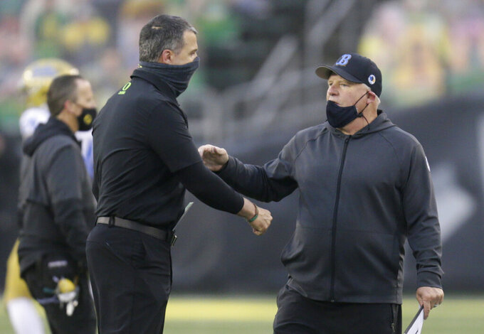Oregon head coach Mario Cristobal, left, and UCLA head coach Chip Kelly meet at midfield after an NCAA college football game Saturday, Nov. 21, 2020, in Eugene, Ore. (AP Photo/Chris Pietsch)