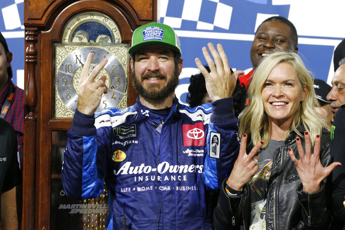 Martin Truex Jr., left, and his girlfriend Sherry Pollex, right, pose with the trophy as he celebrates after winning a NASCAR Cup Series race at Martinsville Speedway in Martinsville, Va., Sunday, Oct. 27, 2019. (AP Photo/Steve Helber)