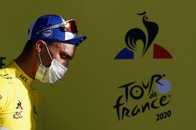 France's Julian Alaphilippe, wearing the overall leader's yellow jersey arrives on podium after winning the second stage of the Tour de France cycling race over 186 kilometers (115,6 miles) with start and finish in Nice, southern France, Sunday, Aug. 30, 2020.(Sebastien Nogier/Pool photo via AP)
