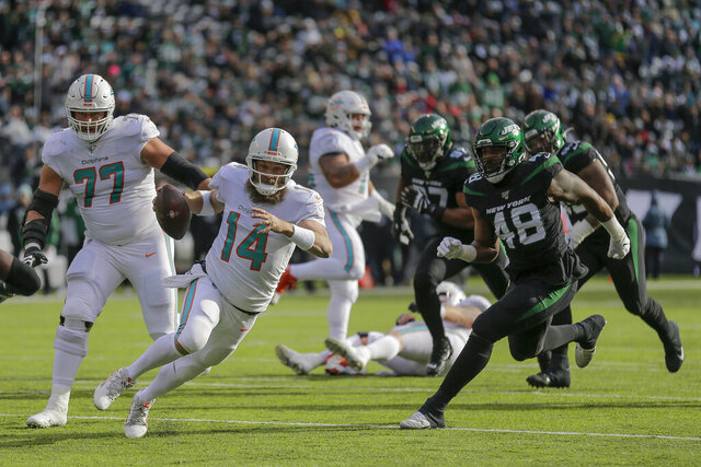 Miami Dolphins quarterback Ryan Fitzpatrick (14) runs the ball against the New York Jets during the first quarter of an NFL football game, Sunday, Dec. 8, 2019, in East Rutherford, N.J. (AP Photo/Seth Wenig)