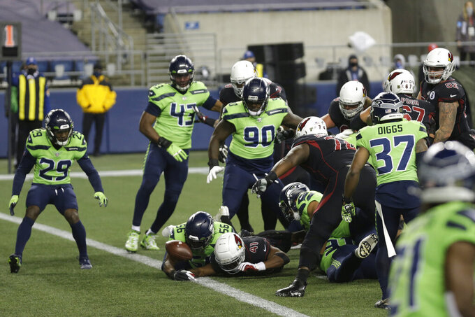 Arizona Cardinals running back Kenyan Drake (41) loses the ball in the end zone in front of Seattle Seahawks linebacker Jordyn Brooks (56) during the first half of an NFL football game, Thursday, Nov. 19, 2020, in Seattle. The play was initially ruled a fumble, but was reversed after an officials' review and ruled a touchdown for the Cardinals. (AP Photo/Lindsey Wasson)