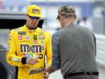 Kyle Busch, left, gives an autograph before qualifying for the NASCAR Daytona 500 auto race at Daytona International Speedway, Sunday, Feb. 10, 2019, in Daytona Beach, Fla. (AP Photo/Terry Renna)