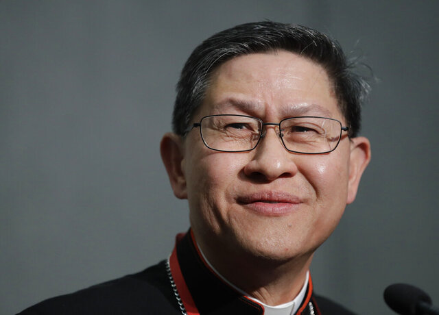FILE - In this Oct. 23, 2018 file photo, Manila Cardinal Luis Tagle smiles as he listens reporters questions during a press conference on the Synod at the Vatican. The Vatican announced on Sunday that Pope Francis named Manila's Cardinal Tagle to a major Vatican post, the Congregation for the Evangelization of the Peoples, in a move that could boost the Asian prelate's chances to perhaps someday become pontiff himself. (AP Photo/Alessandra Tarantino, file)