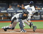 Tampa Bay Rays' Guillermo Heredia, top, beats the throw to New York Yankees catcher Austin Romine to score on Kevin Kiermaier's two-run single during the inning of a baseball game Friday, July 5, 2019, in St. Petersburg, Fla. (AP Photo/Steve Nesius)