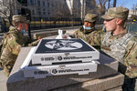 Members of the National Guard receive donated pizza from We The Pizza, on Saturday, Jan. 16, 2021, in Washington, as security is increased ahead of the inauguration of President-elect Joe Biden and Vice President-elect Kamala Harris. (AP Photo/Jacquelyn Martin)