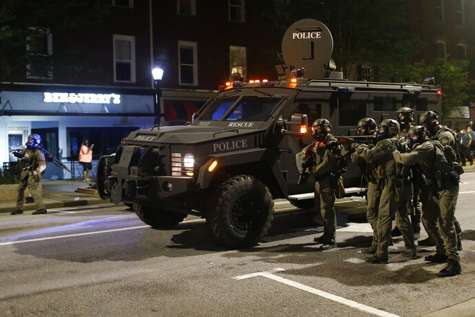 In this Sunday, May 31, 2020 photo, Athens-Clark County police officers in riot gear and backed up by a military vehicle move in on the protesters to remove them from Broad Street in downtown Athens, Ga. The protest was organized to demonstrate the death of George Floyd, who died in police custody in Minneapolis on May 25, sparking demonstrations and riots around the country. (Joshua L. Jones/Athens Banner-Herald via AP)