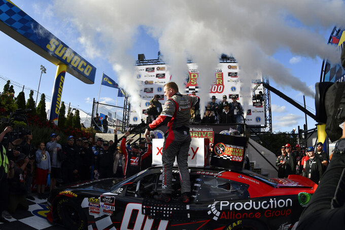 Driver Cole Custer car (#00) celebrates on top of his car in the winners circle during the  NASCAR Xfinity Series auto race, Saturday, Oct. 5, 2019, in Dover, Del. (AP Photo/Brien Aho)