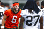 Cleveland Browns quarterback Baker Mayfield (6) laughs while talking to running back Kareem Hunt (27) during an NFL football practice Thursday, Aug. 12, 2021, in Berea, Ohio. (AP Photo/Ron Schwane)