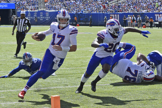 Buffalo Bills quarterback Josh Allen (17), left, runs the ball for a touchdown during the first half of an NFL football game against the New York Giants, Sunday, Sept. 15, 2019, in East Rutherford, N.J. (AP Photo/Bill Kostroun)