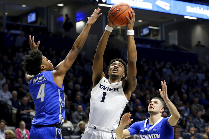 Xavier guard Paul Scruggs (1) drives to the basket as Creighton  guard Shereef Mitchell (4) defends in the first half of an NCAA college basketball game Saturday, Jan. 11, 2020, in Cincinnati. (Kareem Elgazzar/The Cincinnati Enquirer via AP)