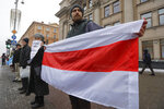 A protester holds a historical Belarusian flag during the