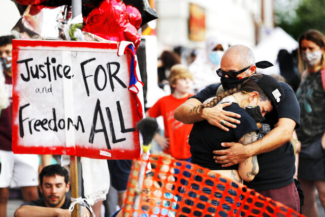 FILE - In this June 3, 2020, file photo, people gather at the site where George Floyd died in Minneapolis. Americans overwhelmingly want clear standards for police on when officers may use force and consequences imposed on cops who do so excessively. That's according to a new poll from the The Associated Press-NORC Center for Public Affairs Research that finds Americans favor significant changes to the country's criminal justice system. (AP Photo/Julio Cortez, File)