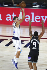 Dallas Mavericks guard Luka Doncic (77) shoots a  3-point basket over Sacramento Kings guard Cory Joseph (9) during the first half of an NBA basketball game Tuesday, Aug. 4, 2020, in Lake Buena Vista, Fla. (Kim Klement/Pool Photo via AP)