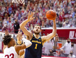 Michigan center Hunter Dickinson (1) shoots over the defense of Indiana forward Trayce Jackson-Davis (23) during the first half of an NCAA college basketball game, Saturday, Feb. 27, 2021, in Bloomington, Ind. (AP Photo/Doug McSchooler)