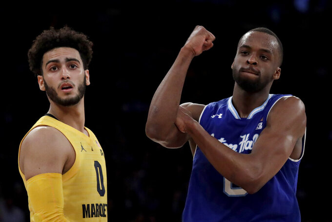 Seton Hall guard Quincy McKnight, right, gestures after scoring a basket as Marquette guard Markus Howard looks on during the second half of an NCAA college basketball semifinal game in the Big East men's tournament, Friday, March 15, 2019, in New York. Seton Hall won 81-79. (AP Photo/Julio Cortez)