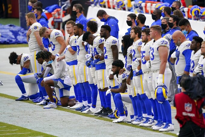 Some Los Angeles Rams players take a knee during the national anthem before an NFL football game against the Washington Football Team Sunday, Oct. 11, 2020, in Landover, Md. (AP Photo/Susan Walsh)