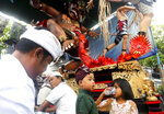 Balinese people sit in front of a giant effigy locally known as