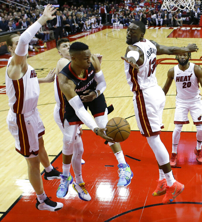 Houston Rockets guard Russell Westbrook, center, passes the ball as Miami Heat forward Kelly Olynyk, left, and center Bam Adebayo defend during the first half of an NBA basketball game, Wednesday, Nov. 27, 2019, in Houston. (AP Photo/Eric Christian Smith)