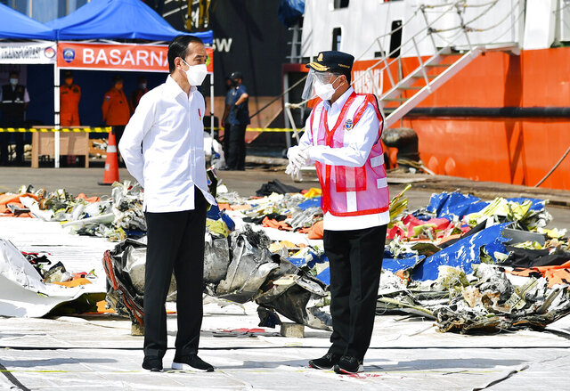 In this photo released by the Indonesian Presidential Palace, President Joko Widodo, left, confers with Transportation Minister Budi Karya Sumadi as they inspect pieces of the Sriwijaya Air flight SJ-182 retrieved from the Java Sea where the passenger jet crashed on Jan. 9, at Tanjung Priok Port in Jakarta, Indonesia, Wednesday, Jan. 20, 2021. The Indonesian leader on Wednesday reassured relatives of the passengers killed when the plane nosedived into the Java Sea that compensation is paid to family members struggled with grief. (Laily Rachev, Indonesian President Palace via AP)