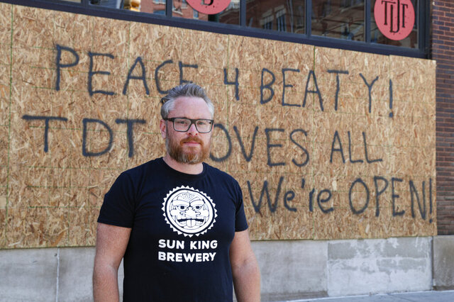 Restaurant owner Michael Cranfill poses in front of sign on the restaurant's boarded up windows in Indianapolis, Tuesday, June 2, 2020 to honor his friend former Indiana University football player Chris Beaty. Beaty was one of two people fatally shot in Indianapolis during protests over the death of George Floyd.(AP Photo/Michael Conroy)