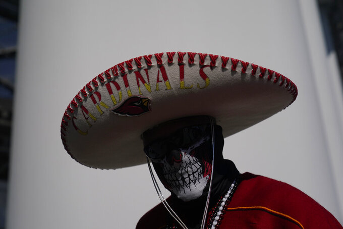 A fan wears a costume before an NFL football game between the Los Angeles Rams and Arizona Cardinals Sunday, Oct. 3, 2021, in Inglewood, Calif. (AP Photo/Jae C. Hong)