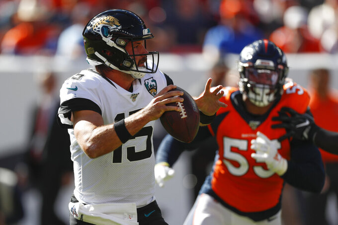 Jacksonville Jaguars quarterback Gardner Minshew, left, scrambles under pressure from Denver Broncos outside linebacker Bradley Chubb, right, during the first half of an NFL football game Sunday, Sept. 29, 2019, in Denver. (AP Photo/David Zalubowski)