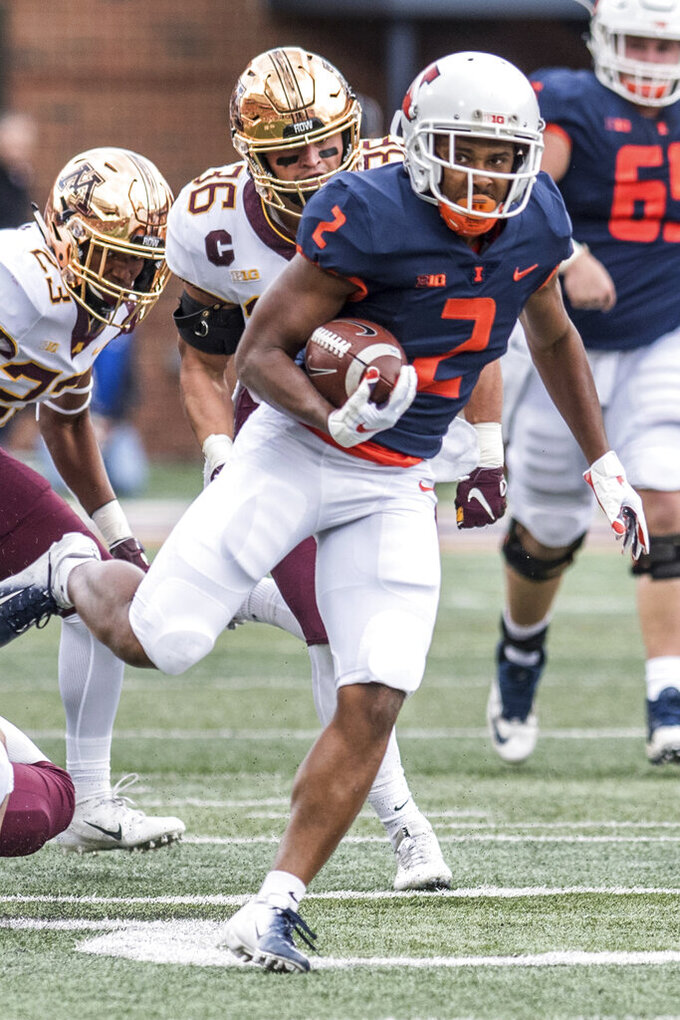 FILE - In this Nov. 3, 2018, file photo, Illinois running back Reggie Corbin (2) breaks a tackle to score Illinois' first touchdown of the game against Minnesota in the first half of an NCAA college football game in Champaign, Ill. Heading into the Year 4 of Lovie Smith's tenure, the Illini are still looking to reach bowl eligibility under the former Super Bowl coach. Corbin, a senior with blazing speed, broke out last season with 1,085 yards rushing on 8.5 yards per carry. (AP Photo/Holly Hart, File)