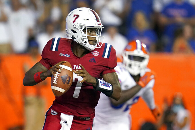 Florida Atlantic quarterback K'Nosi Perry, left, looks for a receiver as he is pressured by Florida linebacker Antwuan Powell during the first half of an NCAA college football game Saturday, Sept. 4, 2021, in Gainesville, Fla. (AP Photo/John Raoux)