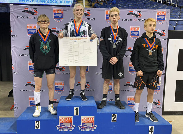 CORRECTS CITY TO GREENSBORO- This photo provided by North Carolina High School Athletic Association (NCHSAA) shows Heaven Fitch, center, Luke Wilson, left, and Hunter Fulp, right, and Brandon Ropp, far right,  after the state wrestling championships in Greensboro, N.C, on Saturday, Feb. 22, 2020.  NCHSAA said on its website that Fitch of Uwharrie Charter became the first female to win one of the association's individual state wrestling championships. She won the 106 pound (48 kg) weight class at the 1A division on Saturday.  (North Carolina High School Athletic Association via AP)