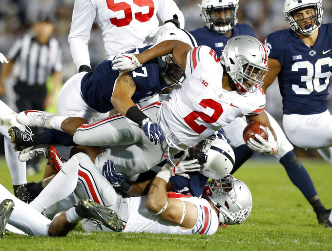 "FILE - In this Saturday, Sept. 29, 2018 file photo, Ohio State's J.K. Dobbins (2) is tackled by Penn State's Koa Farmer (7) during the first half of an NCAA college football game in State College, Pa. J.K. Dobbins wants to make up for his ""failure"" last season. Despite rushing for over 1,000 yards, Dobbins calls 2018 a disappointment. He had a drop-off from his record-breaking freshman year and is determined to get back to that level and prove he's best running back in the nation.(AP Photo/Chris Knight, File)"