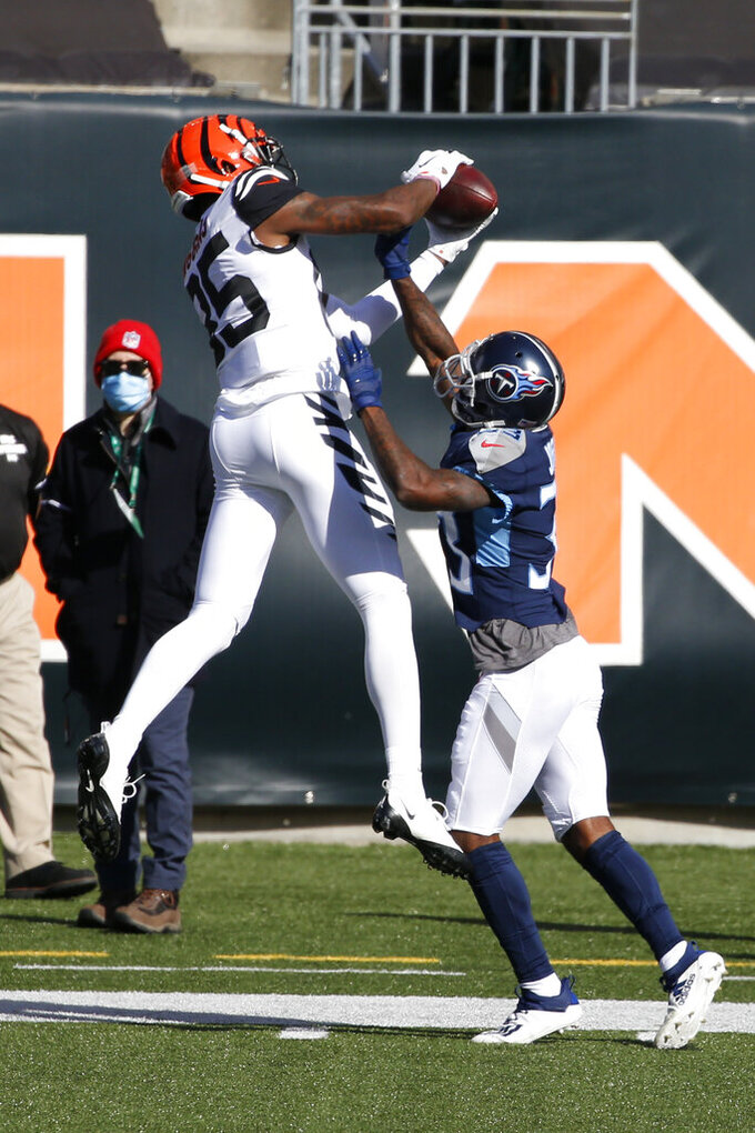 Cincinnati Bengals' Tee Higgins (85) makes a catch against Tennessee Titans' Johnathan Joseph (33) during the first half of an NFL football game, Sunday, Nov. 1, 2020, in Cincinnati. (AP Photo/Gary Landers)